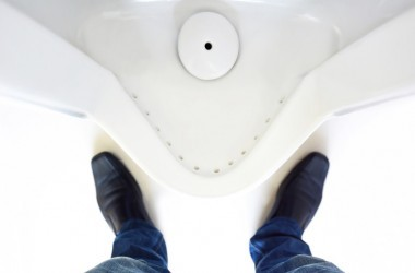Top view of a man's feet in front of urinal in men's bathroom
