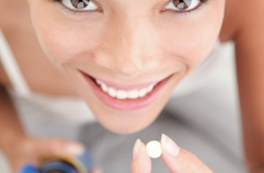 Smiling woman taking a supplement