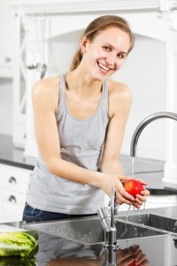 Smiling woman washes an apple lettuce is next