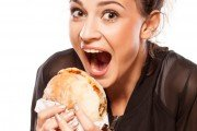 Woman about to take a bit out of a huge burger
