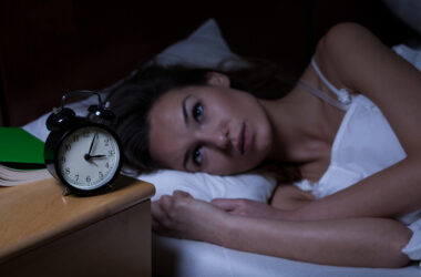 Woman with insomnia lying in bed with open eyes at increased Alzheimer's riskth open eyes open