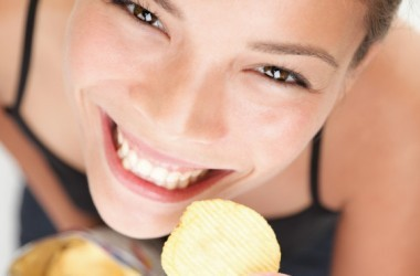 Woman eating a bag of junk food potato chips