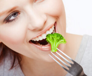 Woman eating breast cancer fighting broccoli off a fork