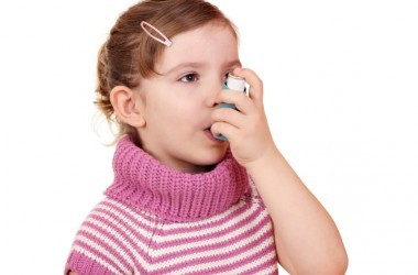 little girl with acetaminophen linked asthma uses inhaler