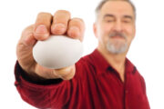 man holding a heart disease fighting white egg in his outstretched hand common food myths