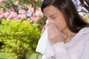 woman with seasonal allergies reacting to spring pollen and sneezing