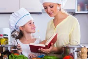 Mother and daughter in chef hats cooking vegetables