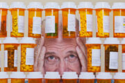 Overmedicated senior man peers through medication bottles