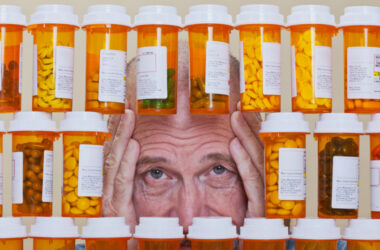 Overmedicated senior man peers through medicine bottles