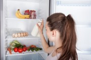 Woman chooses milk from opened refrigerator to check sell by date
