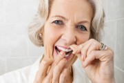 woman flossing her teeth to help prevent pancreatic cancer