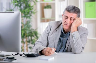 man who needs to naturally boost energy sleeps at desk