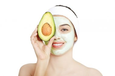 Woman holds an avocado over her moisturizing avocado face mask
