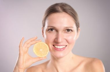 Young woman with beautiful skin holds a lemon half