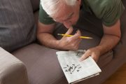 Senior man working on crossword puzzle to fight brain aging