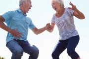 Energetic Senior Couple Bouncing On Trampoline