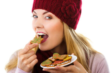 Woman eating a plate of Christmas cookies and not gaining weight