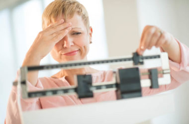 Woman adjusting scale worried about weight gain