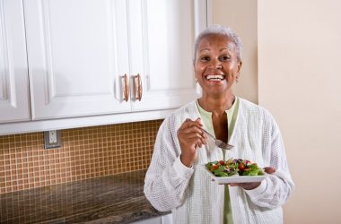 Mature woman eating vitamin K richsalad in kitchen