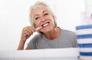 Senior woman in bathroom brushing teeth to prevent swollen painful gums and gingivitis gum disease