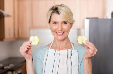Smiling senior woman holding slices of green apple