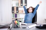 Woman doing chair exercises at her desk getting big exercise benefits
