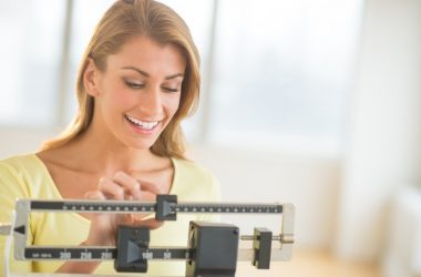 Happy woman weighing herself on a scale