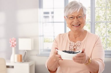 Senior lady with bowl of diabetes fighting blueberries that won't spike your blood sugar