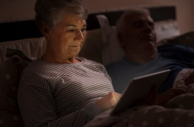Senior woman using her tablet computer in bed at night