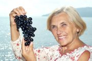 Beautiful senior woman holding a bunch of grapes