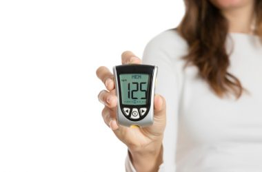 Woman with good blood sugar control holding a glucometer