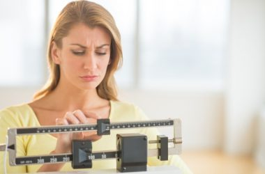 Woman weighing herself has hit a weight loss plateau
