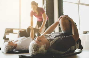 Senior couple lies on ground doing back exercises and stretches