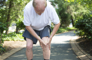 Older main suffering from painful joints grabs his knee