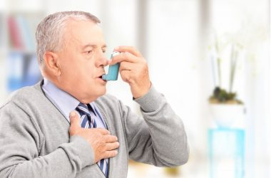 Senior man having a severe asthma attack uses his inhaler to relieve asthma symptoms
