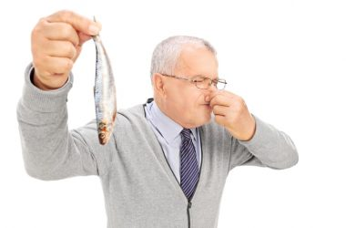 Senior man holding smelly fish has good sense of smell and lower dementia risk