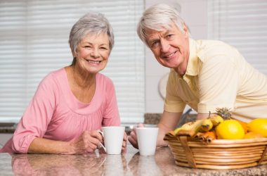 Smiling senior couple with fruit basket to stop overeating and lose weight