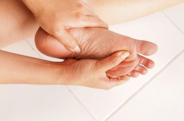 Woman massages achy swollen feet to combat foot problems