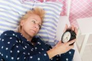 Mature woman in bed with insomnia considers sleep aids for sleep problems