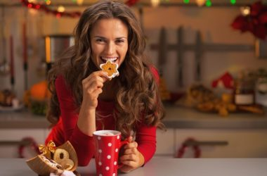 Smiling woman eating Christmas cookie uses tricks to avoid holiday weight gain