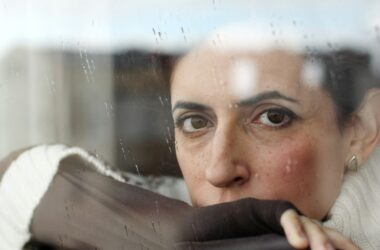 Woman suffering with seasonal depression gazes sadly through a wet window