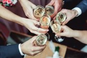 Close up of hands toasting with champagne to illustrate hangover cures