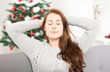 Woman sitting in front of Christmas tree works to reduce stress