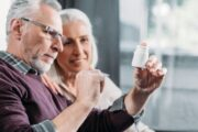 Senior couple looking at pill bottle with supplement to fight Alzheimer's disease