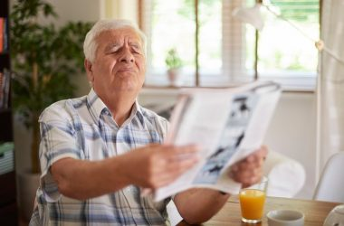Senior man with blurry eyesight caused by high blood sugar has trouble seeing paper