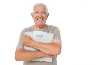 Smiling senior holding scale used weight loss tips to lose holiday pounds