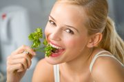 Smiling woman eating parsley with chlorophyll to protect against liver disease