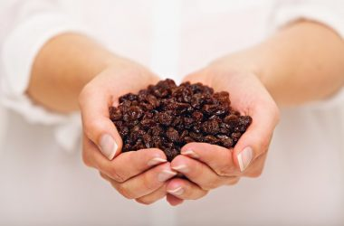 Woman holding a handful or raisins sold as health foods