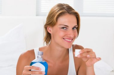 Woman holding bottle of mouthwash which may raise risk of diabetes