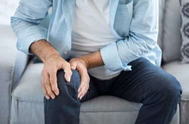 Man suffering from arthritis pain grasps his painful knee